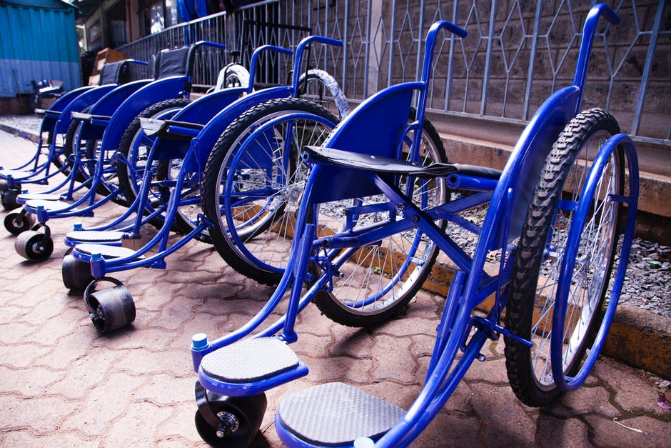 Blue wheelchairs lined up for the use of people